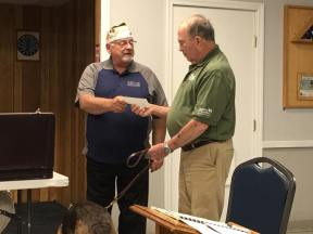 Commander Barrett giving VetDOGS a check from our fundraiser